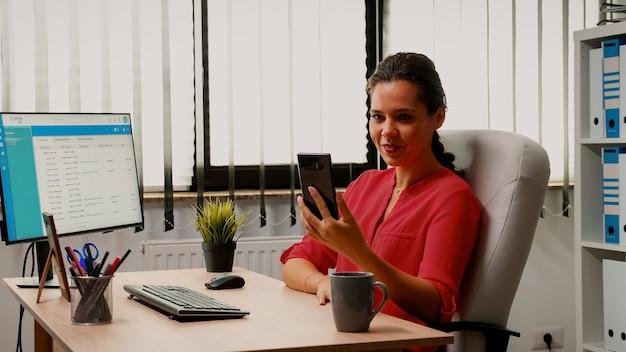 現代のオフィスで電話のウェブカメラを使用して同僚と話しているフリーランサー。オンライン会議、インターネット技術を使用したウェビナーでチャットについて話し合うビジネスリモートチームと協力する起業家