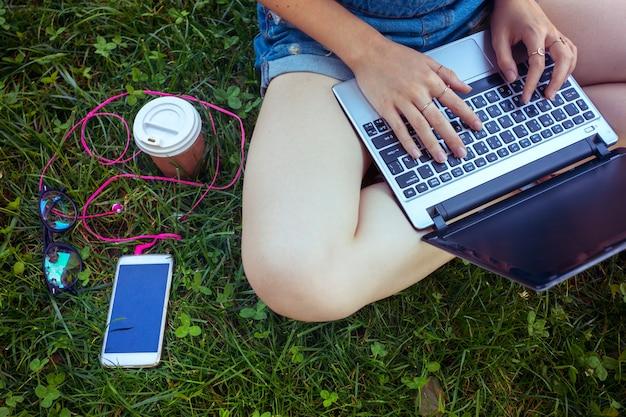 Фрилансер - девушка сидит с ноутбуком на зеленой лужайке