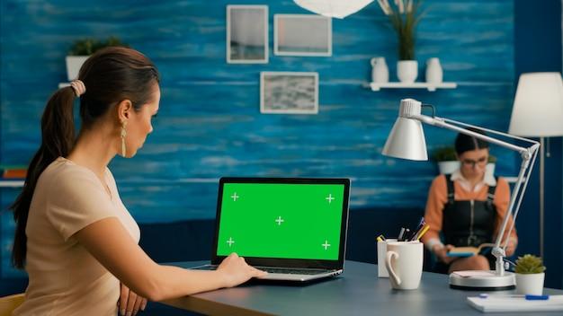 机のテーブルの上に立っている企業のためのモックアップグリーンスクリーンクロマキーを備えたコンピューターを使用しているフリーランサー。ホームオフィスのコマースプロジェクトで働く孤立したホームオフィスのpcを使用している女性