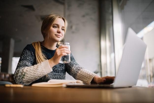Фрилансер, используя ноутбук, печатать на клавиатуре, пить кофе в офисе