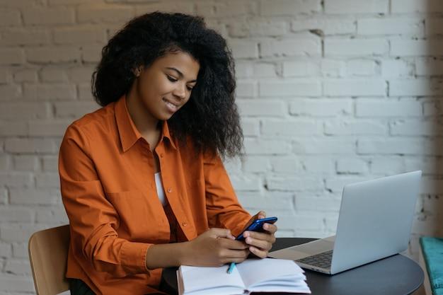 携帯電話、ラップトップ、インターネットを使用したフリーランサー、メールの確認、コミュニケーション、在宅勤務