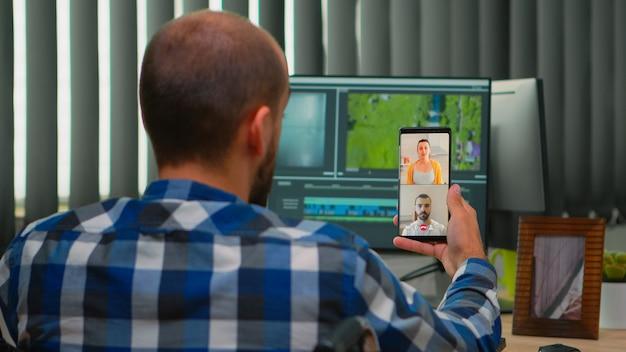 Editor video freelance con disabilità in sedia a rotelle che ha videochiamata durante la modifica della postproduzione di un progetto che crea contenuti nel moderno ufficio dell'azienda. videografo che lavora da studio fotografico
