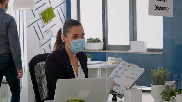 Freelancer wearing face mask to prevent infection with covid19 while showing financial graphs to her collegue. business team keeping ing ing social distancing while working in company office