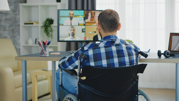 Freelancer in wheelchair waving during a business video call while working from home office.
