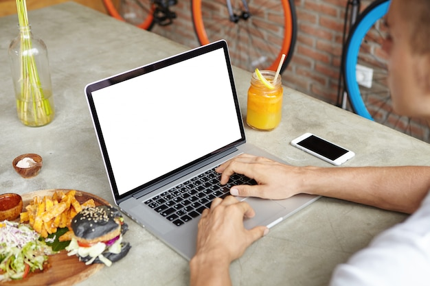 Freelancer in white t-shirt working remotely using laptop computer during lunch, sitting at cafe table with burger