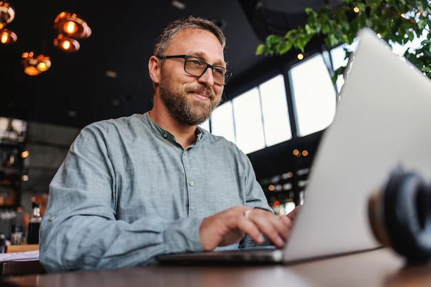 レストランに座ってノートパソコンを使用してレポートを入力する眼鏡をかけたフリーランサー