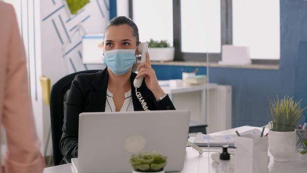 Фрилансер с лицевой маской разговаривает по телефону, проверяя финансовые отчеты на портативном компьютере в новом обычном офисе компании. коллеги сохраняют социальное дистанцирование, чтобы избежать вирусных заболеваний