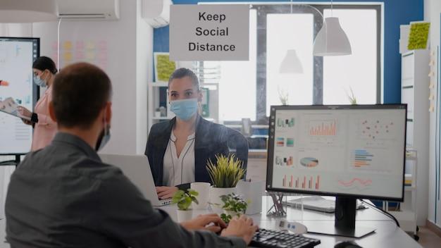 営業所に座っているpcの金融グラフィックスで働いているフェイスマスクを持つフリーランサー。 covid19の感染を防ぐために、マーケティングマンテンの社会的距離についてバックグラウンドで話している同僚