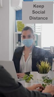 안면 마스크를 쓴 프리랜서가 사무실에 앉아 있는 pc의 금융 그래픽 작업을 하고 있습니다. 마케팅에 대해 배경으로 이야기하는 동료들은 covid19 감염을 방지하기 위해 사회적 거리를 유지합니다