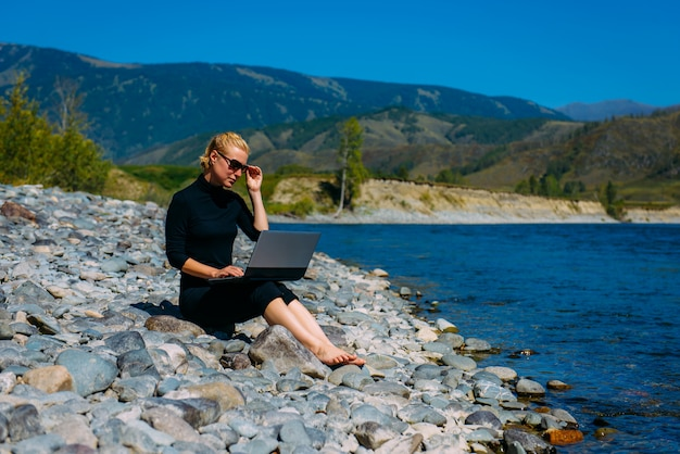 Freelancer with laptop on the nature. blogger hipster traveler business lady pretty girl  works outdoor. young blondy woman in black sitting next to mountain river.