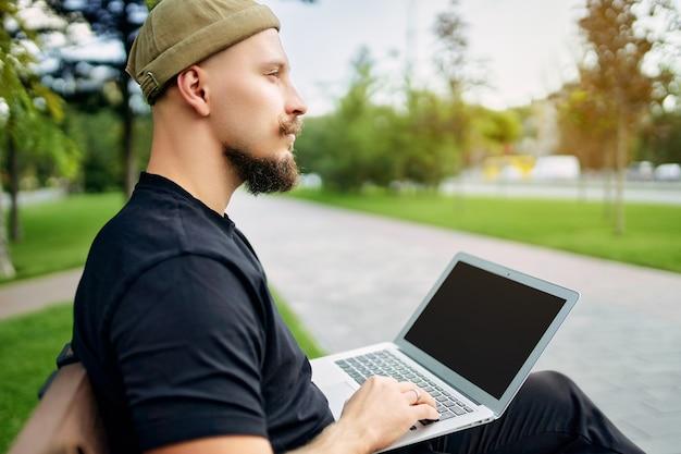 노트북이 있는 프리랜서는 블로거 힙스터 여행자 젊은 세련된 남자가 일하는 동안 도시 공원에 앉아 있습니다.