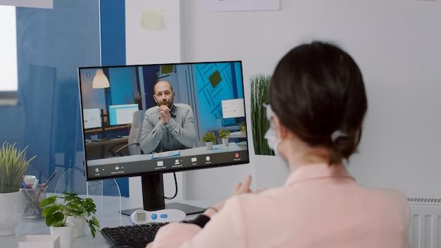 보호용 안면 마스크를 쓴 프리랜서는 새로운 일반 비즈니스 사무실에 앉아 가상 회의를 하는 동안 컴퓨터에서 경영진과 이야기합니다. 코로나바이러스 전염병 동안 일하는 백인 여성