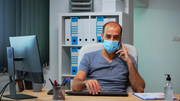 パンデミック時に事務室の机の上に座って、パートナーと携帯電話で話している保護マスクを持つフリーランサー。スマートフォンで話す書き込みをチャットする新しい通常のオフィスで働くフリーランサー