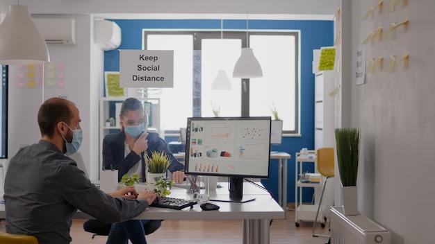 チームと電話で話している間ラップトップコンピューターで動作する保護医療フェイスマスクを持つフリーランサー。 covid19検疫中に新しい通常の会社のオフィスの机のテーブルに座っている実業家