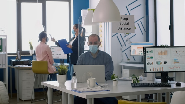 Freelancer with protective face mask checking collegues temperature with thermometer while working in company office during covid19 epidemic. coworkers keeping social distance to prevent covid19