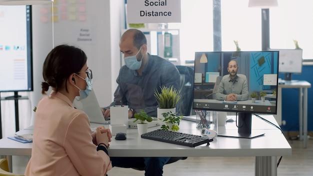 보호용 안면 마스크를 쓴 프리랜서는 비즈니스 사무실에 앉아 가상 화상 통화 회의 중에 동료와 이야기합니다. covid19 감염 예방을 위해 사회적 거리를 유지하는 동료