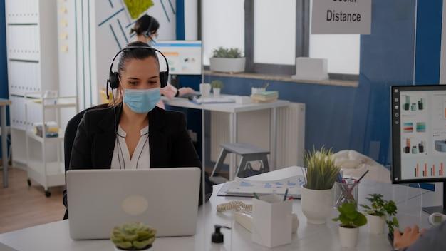 ビジネス会議についてマイクに向かって話している間、ヘッドセットを身に着けている保護フェイスマスクを持つフリーランサー。コロナウイルスパンデミックの間に会社のオフィスでラップトップコンピューターに取り組んでいる実業家