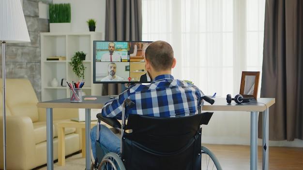 Фрилансер с инвалидностью при ходьбе в инвалидной коляске во время бизнес-видеовстречи в интернете.