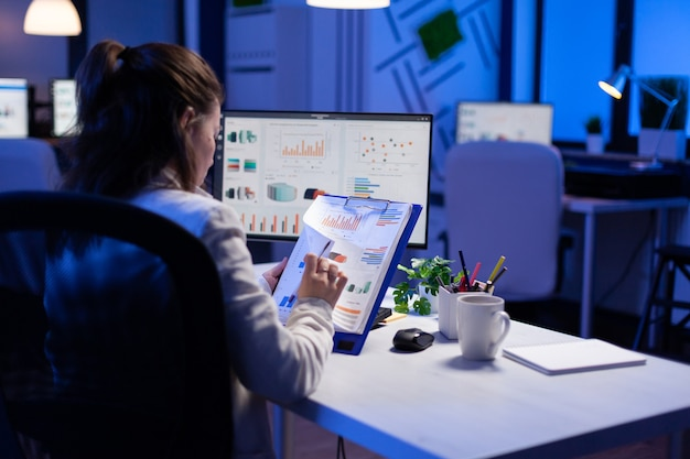 Freelancer woman comparing graphics from clipboard with grafics from computer at business office