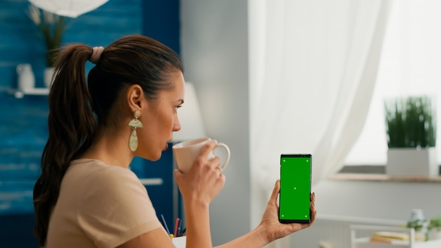 Freelancer woman drinking coffee in office desk talking with collegue using mock up green screen chroma key smartphone. caucasian female searching online information use isolated phone