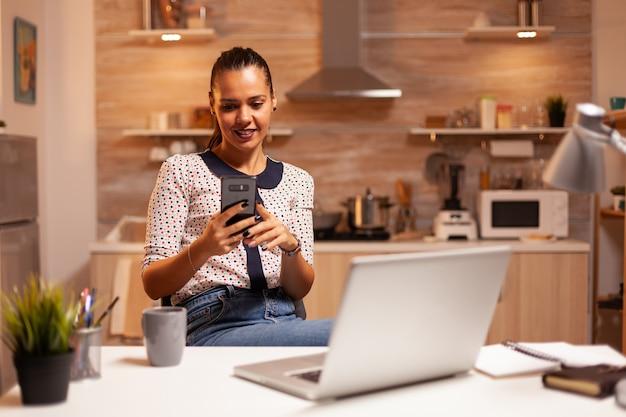 Женщина-фрилансер разговаривает по телефону, работая из дома поздно ночью. сотрудник, использующий современные технологии в полночь, выполняет сверхурочную работу по работе, бизнесу, карьере, сети, образу жизни, беспроводной связи