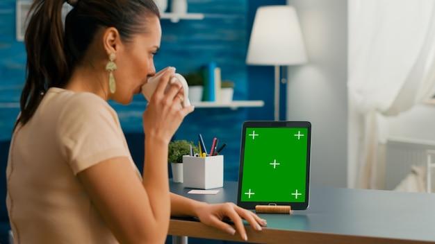 Фрилансер женщина, держащая чашку кофе, смотрящую на планшетный компьютер с макетом зеленого экрана цветности ключа, сидящего на столе стола. кавказская женщина просматривает изолированное устройство из комнаты домашнего офиса