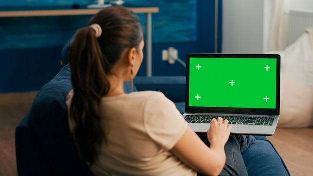 Freelancer woman sitting on sofa in home office typing on laptop computer with mock up green screen chroma key display. caucasian woman working on financial graphs using isolated pc