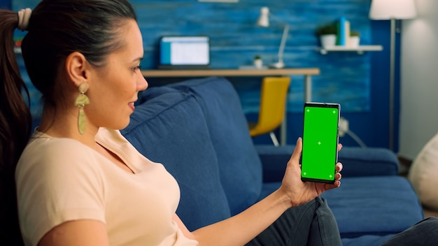 Freelancer woman sitting on sofa in living room, looking at isolated smartphone with green screen chroma key in landscape mode