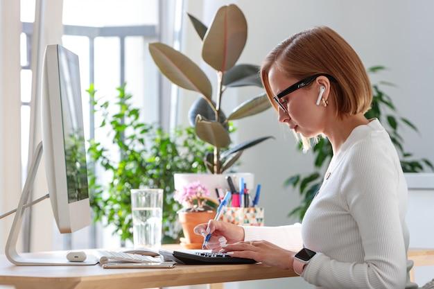 ペンでメモを取るフリーランサーの女性がコンピューターで作業し、計算機を使用して、植物に囲まれた請求書を計算します。距離の仕事。