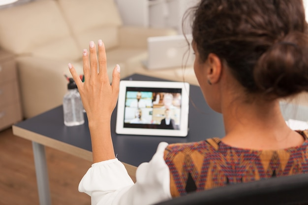 Freelancer woman waving during a video call on tablet computer.