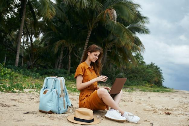 海で砂のラップトップを持つフリーランサー女性