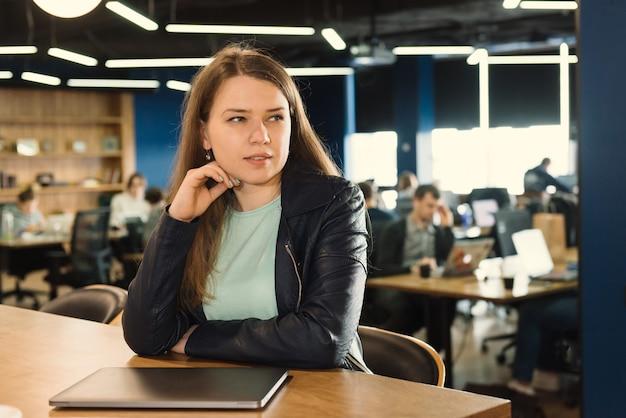 Женщина-фрилансер, работающая в коворкинге или творческом пространстве, сидит возле ноутбука над группой людей