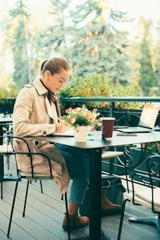 リモートから働くフリーランサーの女性、カフェに座ってプランナーで書く女性