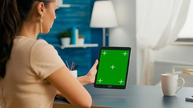 녹색 화면 크로마 키 디스플레이가 있는 태블릿 컴퓨터를 사용하여 온라인 프로젝트에 대한 커뮤니케이션 아이디어를 작업하는 프리랜서 여성. 강력한 격리 장치를 갖춘 사무실 공간