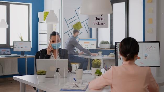 新しい通常の会社のオフィスに座って新しい戦略のために電話で話し合っている保護マスクを持つフリーランサーの労働者。 covid19ウイルスの感染を避けるために社会的距離を尊重するチームワーカー