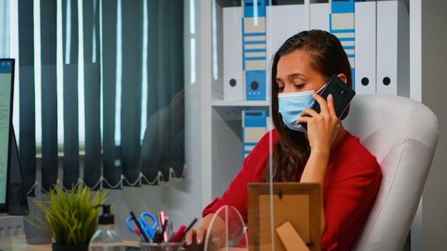 コロナビルのパンデミック時に保護フェイスマスクを着用して職場に座って電話で働いて話しているフリーランサー。コンピューターの前でスマートフォンで話すリモートチームとチャットする女性
