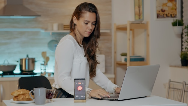 Freelancer working from house with automation lighting system sitting in kitchen turning on lights using voice command to smart home application on smartphone