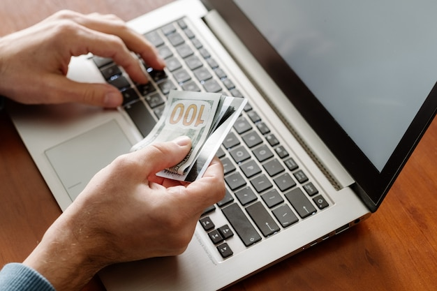 Фрилансер работает не выходя из дома. человек получает зарплату в интернете. мужские руки, держащие деньги