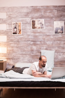 Freelancer working on laptop at night while laying in bed