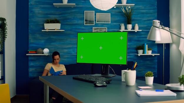 机のテーブルに座っているモックアップグリーンスクリーンクロマキーディスプレイを備えた強力なコンピューターで作業しているフリーランサー