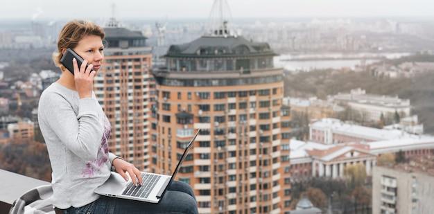 高層ビルの屋上で働くフリーランサー