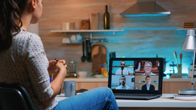 夜にキッチンに座っているラップトップを使用してオンラインでパートナーとリモートで話し合っているフリーランサー。深夜に仮想会議で残業をしている最新のテクノロジーネットワークワイヤレストークを使用する