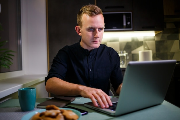 A freelancer works from home in the kitchen and using a laptop. successful man working with a laptop and reading good news. handsome successful entrepreneur sits and works in his modern home.