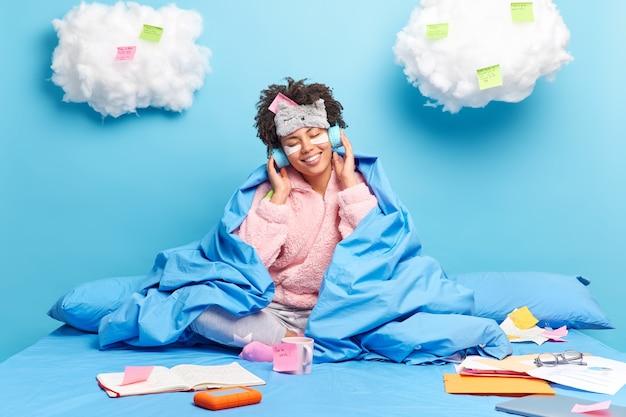 Фрилансер работает из дома, сидит в постели в пижаме, слушает музыку в наушниках, делает заметки, использует наклейки, изолированные на синем