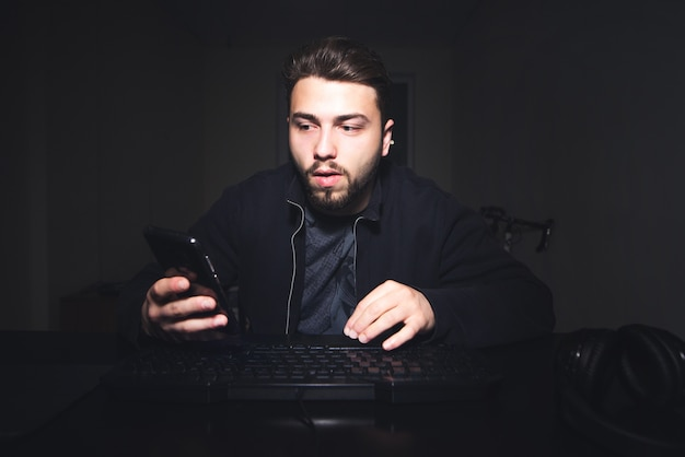Freelancer, works at home on computer and looks at the phone screen