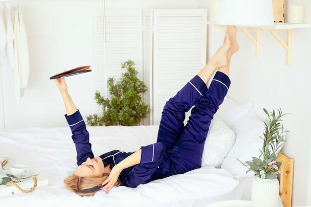 프리랜서는 태블릿과 함께 침대에서 잠옷을 입고 일합니다.