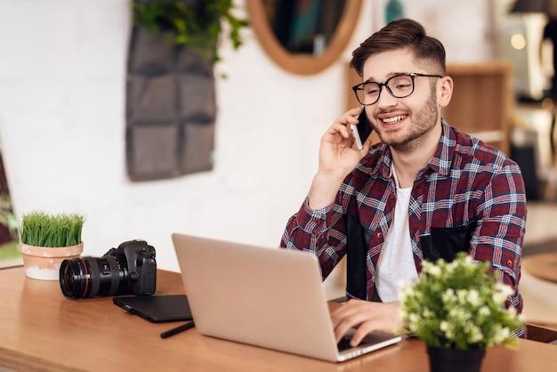 Фотограф freelancer говорит по телефону во время работы.
