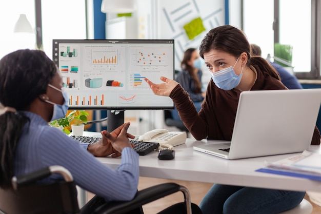 Фрилансеры в защитных масках работают за компьютером в бизнес-офисе во время глобальной пандемии