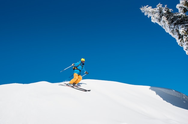 Freeride skier riding down the slope in the mountains