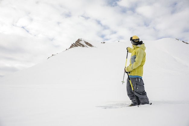 Freeride snowboarder dressed in yellow sportswear looking at mountain